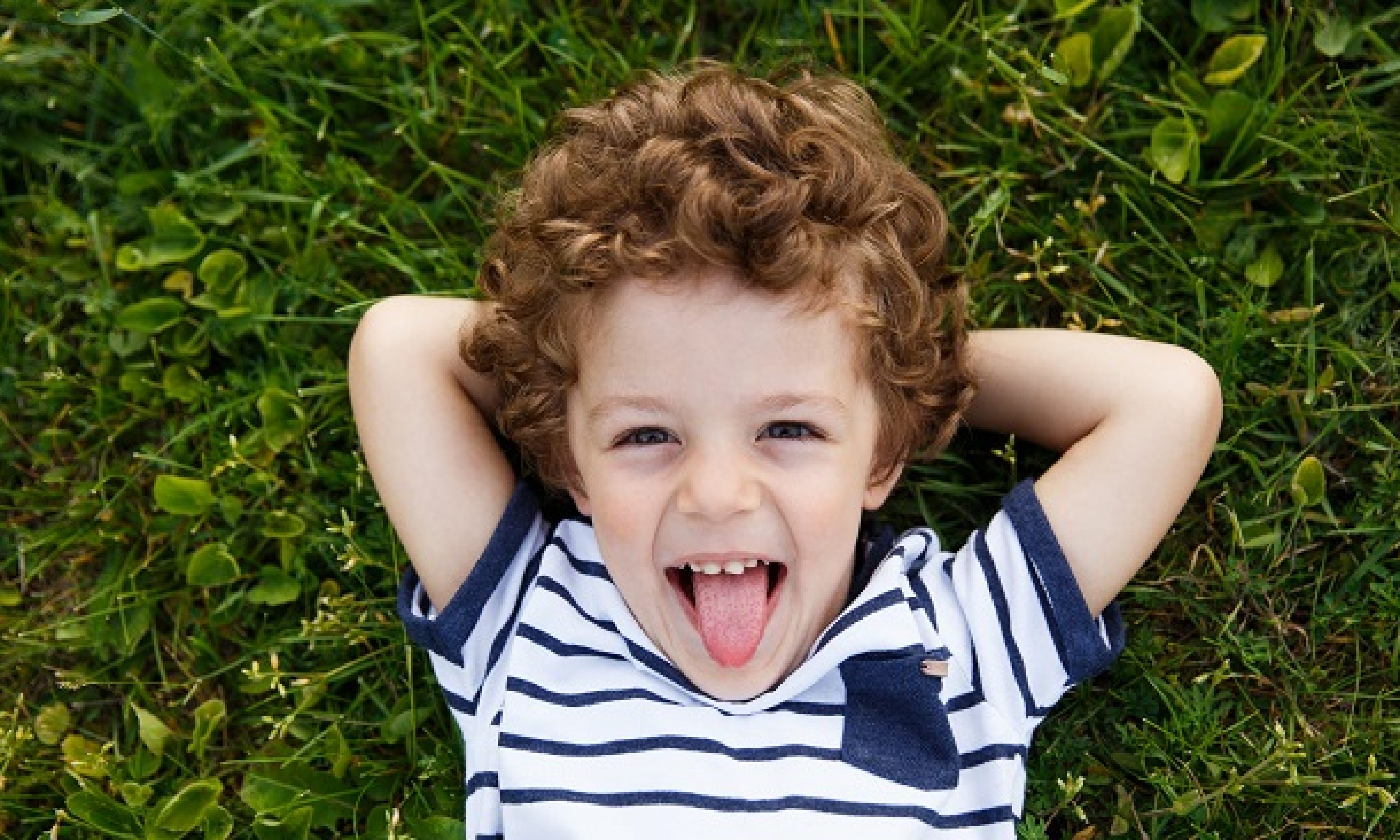 Curly-haired boy in striped t-shirt with hands behind head lying on grass smiling and sticking out tongue.